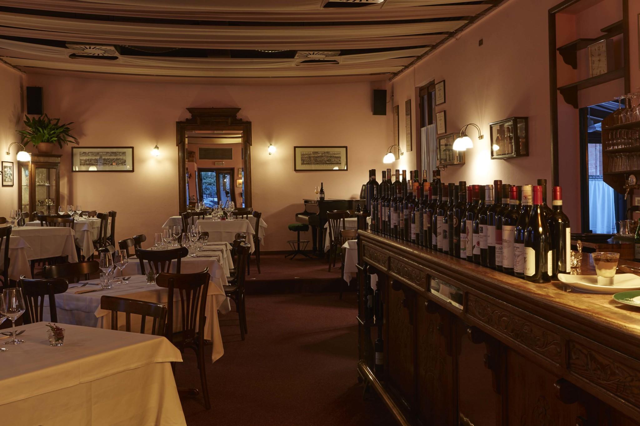 osteria grand hotel sala interna, atmosfera calda, bancone bar con bottiglie di vino